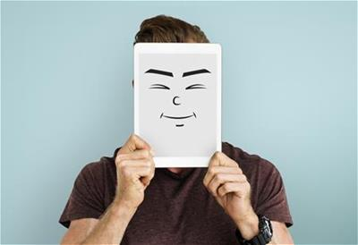 Person holding tablet with face drawn on it.