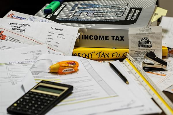 A pile of papers and receipts with tax books, a calculator and some office supplies.