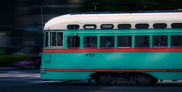 Fast-moving teal and red trolley.