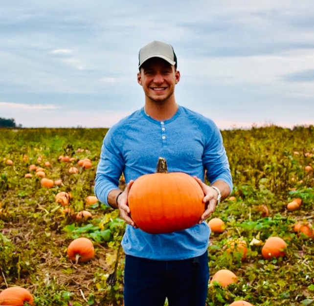 Man smiling and holding a pumpkin in a pumpkin patch.